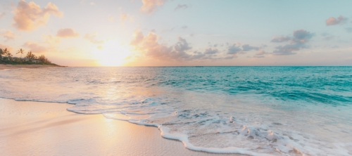 This_is_an_image_of_a_beach_with_calm_blue_water_at_sunset.jpg